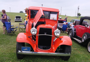 An orange antique car with its hood open.