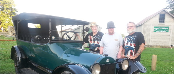 Three men standing behind an antique car.